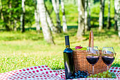 red wine and ripe grapes lie on a tablecloth on a lawn oklo basket for a picnic