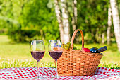 wicker basket for a picnic with fruit and red wine on a tablecloth in a park for two lovers