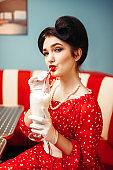 Sexy pin up girl drinks milkshake through a straw