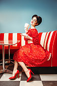Pin up girl drinks coffee in retro cafe
