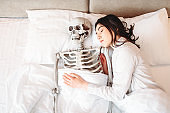 Woman sleeping in bad with funny human skeleton