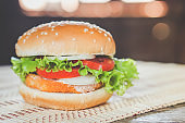 tasty burger homemade closeup on wooden table, fast food unhealthy eating