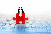 two businessman handshake icon on red jigsaw with people connection in background idea for business teamwork,