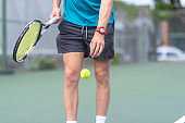 A young male tennis player serving the ball