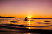 Sunset in Bali and surfer waiting for wave