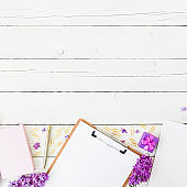 Beauty blog concept with clipboard, notebook, lilac, gift box and accessories on wooden background. Flat lay, top view.