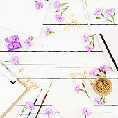 Blogger workspace with clipboard, notebook, pink flowers and accessories on rustic wooden background. Beauty blog concept with copy space. Flat lay, top view.