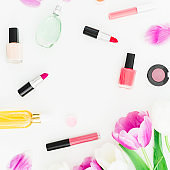 Frame with tulips flowers and cosmetics with perfume on white background. Top view. Flat lay feminine desk.