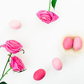 Easter egg and quail eggs in nest and pink roses on white background. Top view, Fat lay. Easter holiday concept.