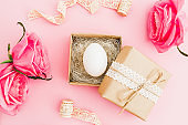 Easter egg in paper gift box and roses flowers on pastel pink background, top view, flat lay, Easter holiday concept.