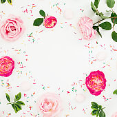 Spring time frame. Floral composition of pastel pink roses flowers and bright confetti on white background. Flat lay, top view.