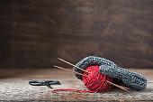 Grey wool mitten with red tweed yarn ball and knitting needles