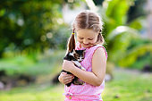 Little girl holding baby cat. Kids and pets