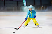 Children play ice hockey. Kids winter sport.