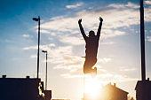 Silhouette of female winner jumping of joy