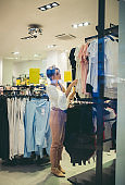 Woman chooses clothes in the boutique, shopping center or store.