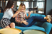 Two women entertained by mobile phone