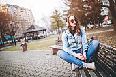 Woman sitting on bench in park and listening a music on headset.