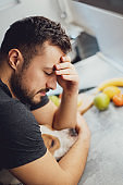 Man hugging his dog while having headache in the kitchen