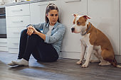 Woman sitting on the kitchen floor mad on her dog