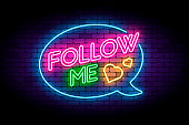Follow me neon sign on the brick wall with hearts and speech bubble.