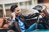 Fashion man sitting in luxury retro cabriolet car outdoors using phone