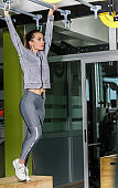 Beautiful young woman hanging on pull ups bar