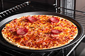 Cooking homemade pizza with salami sausage