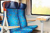 Two blue seats and a desk with an electric drawer in the interior of a fast-moving train in the Czech Republic, Europe