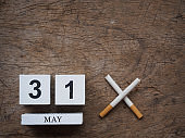 31 MAY wooden calendar block and broken cigarette on wooden texture background top view. World no tobacco concept.