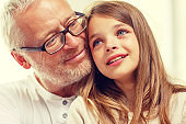 grandfather with crying granddaughter at home