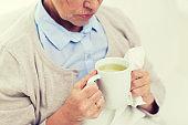 close up of sick senior woman drinking tea at home