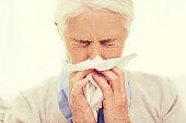 sick senior woman blowing nose to paper napkin