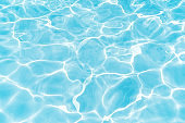 Blue and bright water surface with sun refection in swimming pool for background