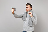 Concerned young man in gray sweater, scarf holding thermometer, doing selfie shot on mobile phone, making video call isolated on grey background. Health ill sick disease treatment cold season concept.