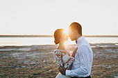 Beautiful wedding photosession. Handsome unshaved groom in a black trousers and young cute bride in white lace pattern dress with exquisite hairstyle on walk along the coastline near the sea sunset