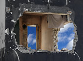 hole and sky between the walls of a destroyed house