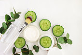 Cucumber slices, cosmetic cream jar and tonic mineral water in bottle, fresh green eucalyptus leaves, viewed above white background.