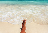 Relaxing on beautiful beach near turquoise sea. Calm foamy waves oncoming on young woman tanned feet resting on sand