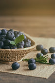 Fresh wild blueberries heap in wood basket on sack put on wooden table under sunlight in vertical for background. Blueberry is healthy and delicious fruits which have high antioxidant and vitamin C.