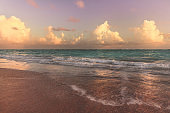 Beautiful serene view on ocean with calm foamy waves at sunrise, warm pink pastel colors