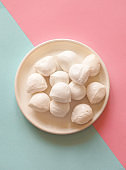Italian mozzarella cheese in bowl on the blue-pink background.