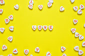 Word love on yellow background made of small hearts
