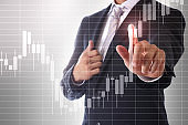 A businessman pointing to a stock chart