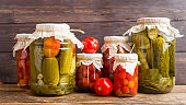 Homemade canned vegetables in cans. Pickled tomatoes and cucumbers in a rural style.