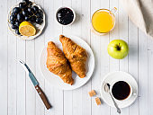 Breakfast on a White Table Coffee Croissant Orange juice Grapes Apple Chocolate