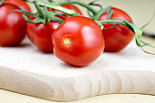 Tasty and ripe cherry tomatoes with droplets of water. Washed vegetables on a bright kitchen table. Dark background.