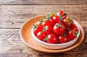 Cherry tomatoes red in ceramic bowl on wooden background