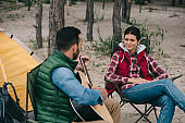 man playing acoustic guitar for smiling wife on camping