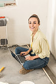 attractive young woman using laptop and smiling at camera during home improvement
